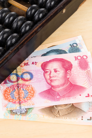 yuan: Old abacus with chinese money yuan banknote Stock Photo