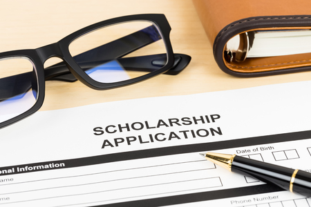 scholarship: Scholarship application form with glasses and pen