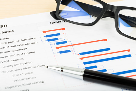 Project management and gantt chart with glasses and pen Stockfoto