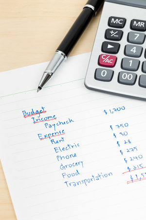 budget: Hand writing home budget with calculator
