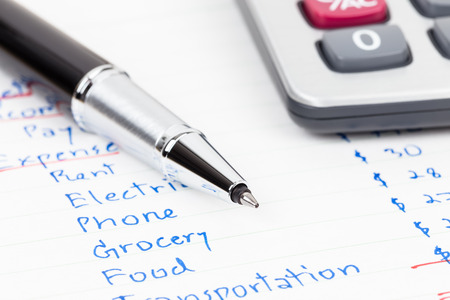 monthly salary: Hand writing home budget with calculator