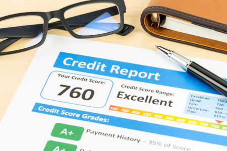 Credit score report with pen, glasses, and organizer book