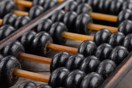 calculator chinese: Old abacus on wooden background close-up