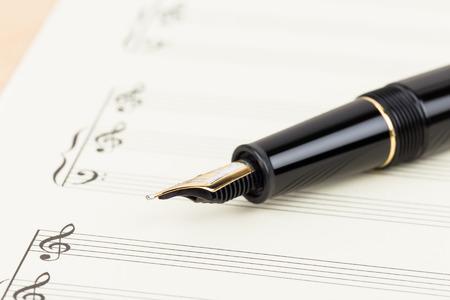 hoja en blanco: cuenta de la música en blanco en el papel de color crema con la pluma