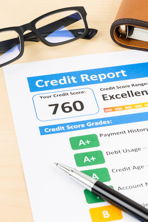 creditworthiness: Credit score report with pen, glasses, and organizer book