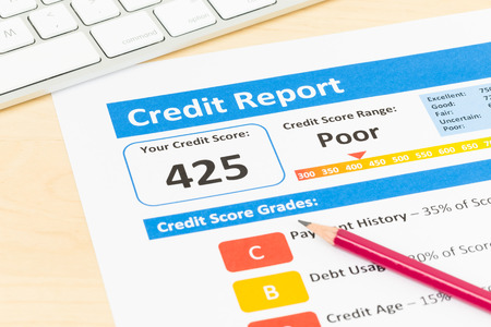 credit report: Poor credit score report with pen and keyboard