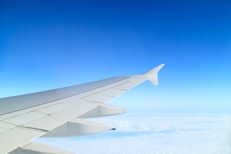 through window: Airplane wing above cloud seen through window Stock Photo