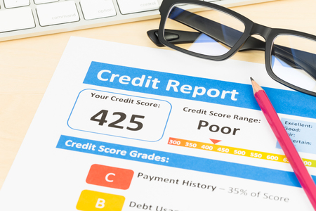 unacceptable: Poor credit score report with pen and keyboard; report is mock-up Stock Photo