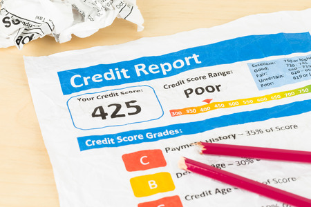 score: Poor credit score report on wrinkled paper with pen and calculator Stock Photo