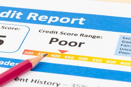 credit report: Poor credit score report with pen and calculator