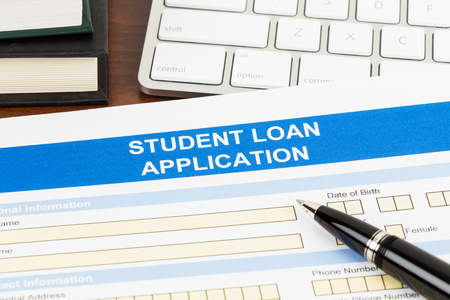 Student loan application form with pen, keyboard, and text book
