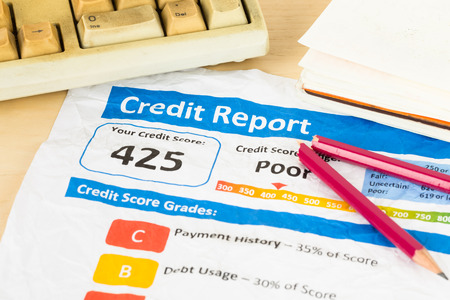 score: Poor credit score report on wrinkled paper with pen and keyboard