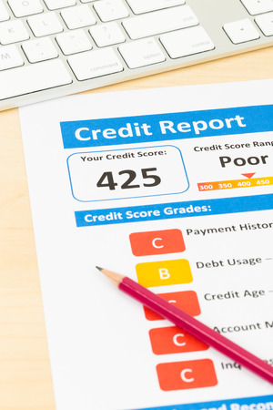 unacceptable: Poor credit score report with pen and keyboard