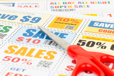 thrifty: Saving discount coupon voucher with scissors, coupons are mock-up