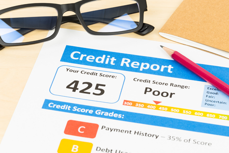credit score: Poor credit score report with pen and calculator