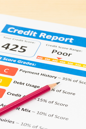 registros contables: Poor credit score report with pen and calculator; document and the report are mocked-up