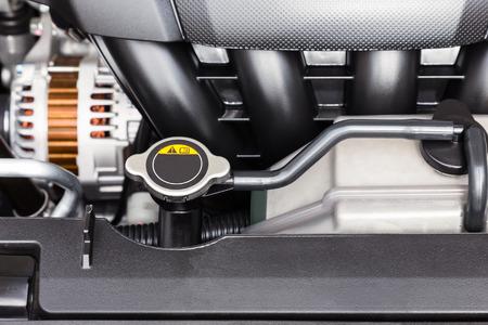 Car engine radiator cap and coolant container close-up