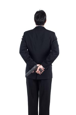 Businessman hiding gun concpet for dishonesty