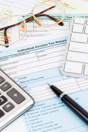 Tax form with calculator, glasses, keyboard, and pen; document are mock-up