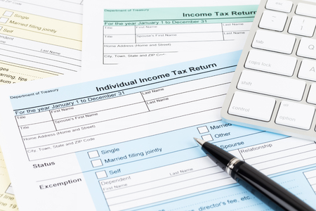 Tax form with keyboard, and pen; document are mock-up