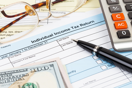 Tax form with calculator, pen, glasses, and dollar banknote; document are mock-up Stock Photo