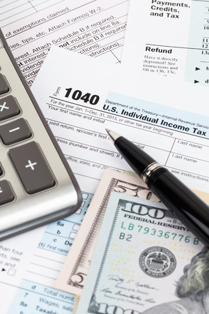 Tax form with calculator, pen, and dollar banknote Stock Photo