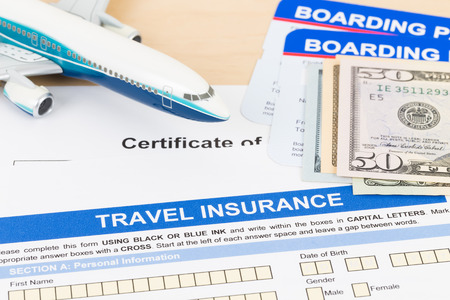 Travel insurance application form with plane model, dollar banknote money, and boarding pass