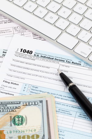 Tax form with keyboard, pen, and dollar banknote