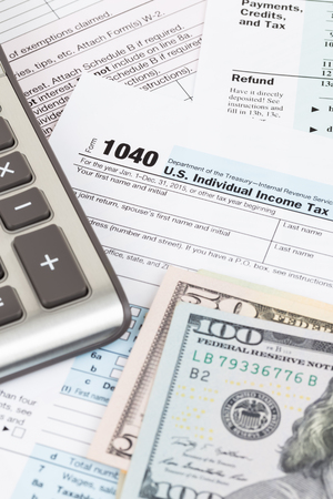 Tax form with calculator and dollar banknote