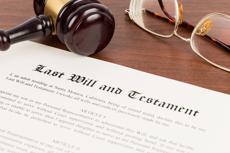 Last will and testament on yellowish paper with wooden judge gavel; document is mock-up Banco de Imagens