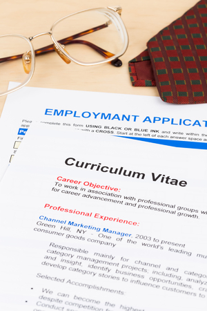 Curriculum vitae and employment application form with glasses and neck tie; documents are mock-up Stock Photo