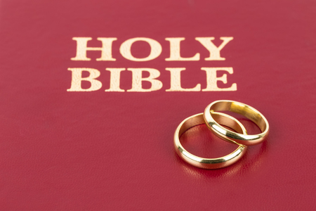 christian marriage: Gold wedding rings on red bible book cover Stock Photo