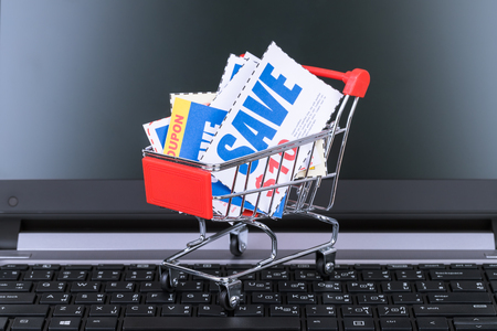 Saving discount coupon voucher in shopping cart and computer notebook, coupons are mock-up Stock Photo