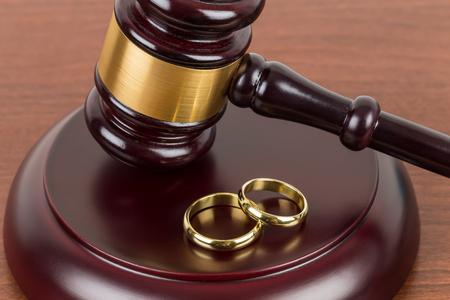Houten rechter hamer en gouden ringen scheiding concept