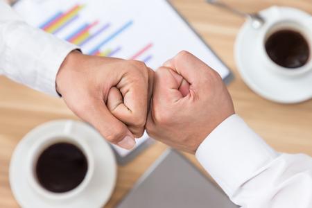 Aziatische bedrijfsmensen die de bovenkant hoogste mening geven van de vuistbuil succesvolle overeenkomst Stockfoto