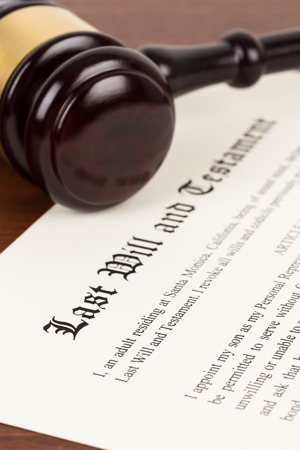 Last will and testament on yellowish paper with wooden judge gavel; document is mock-up 스톡 콘텐츠