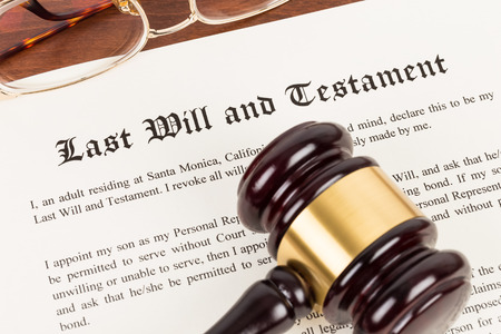 Last will and testament on yellowish paper with wooden judge gavel; document is mock-up Stockfoto