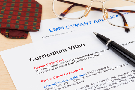 Curriculum vitae and employment application form with glasses and neck tie