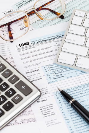 Tax form with calculator, pen, glasses, and keyboard
