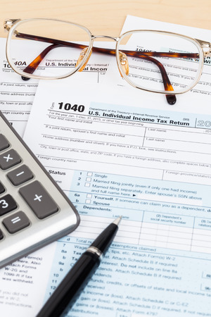 Tax form with pen, glasses, and calculator Stock Photo