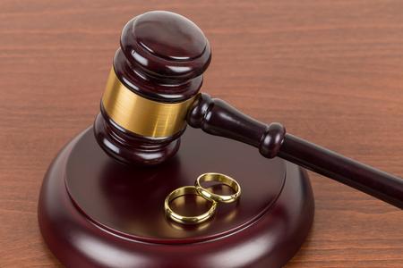 Houten rechter hamer en gouden ringen echtscheiding concept