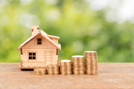 Model house and coin stack on green tree background mortgage saving concept Stock fotó