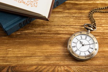 Vintage pocket watch clock with book on wooden background Standard-Bild