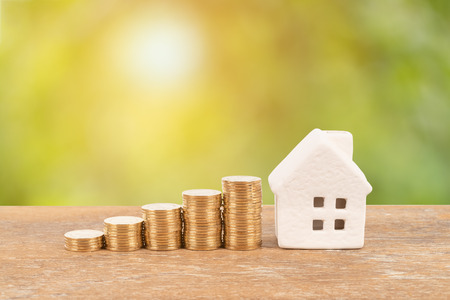 Model house and coin stack on blur green tree background mortgage saving concept