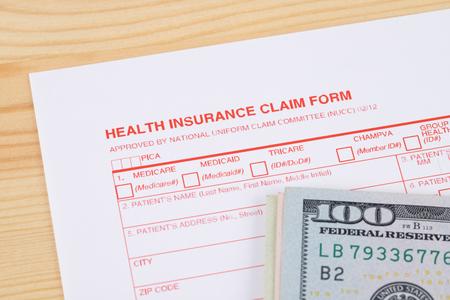 Health insurance claim form on wooden desk Banco de Imagens
