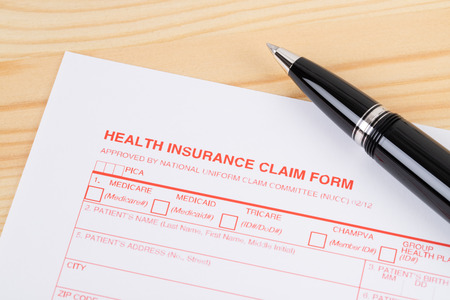 Health insurance claim form with pen on wooden desk