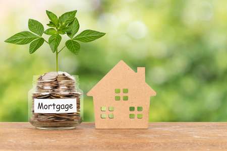 Model house and money coin jar on green tree background mortgage saving concept Imagens - 122847353