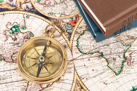 Compass on vintage ancient map with book, concept for direction transportation and travel
