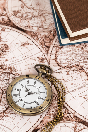 Vintage pocket watch clock on ancient map background with books 版權商用圖片