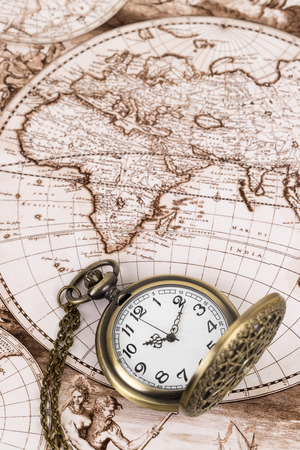 Vintage pocket watch clock on ancient map background